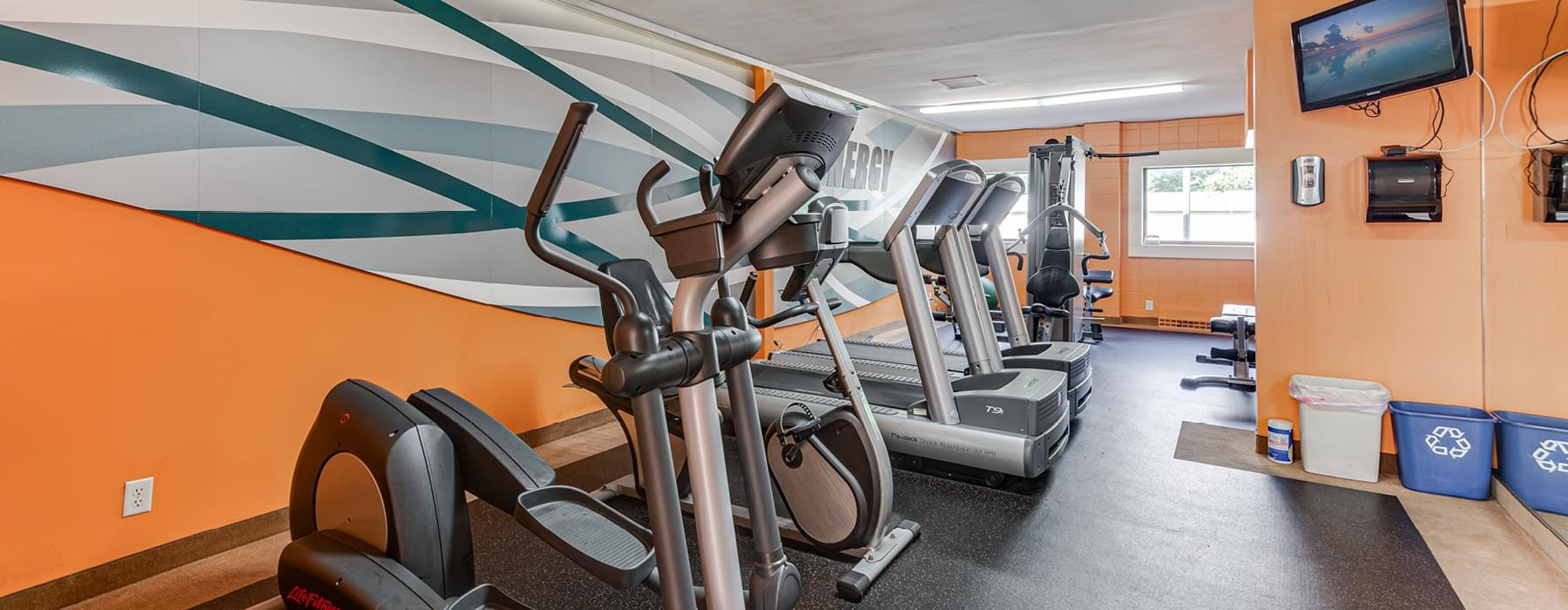 fitness center, well lit by windows and fluorescent lights